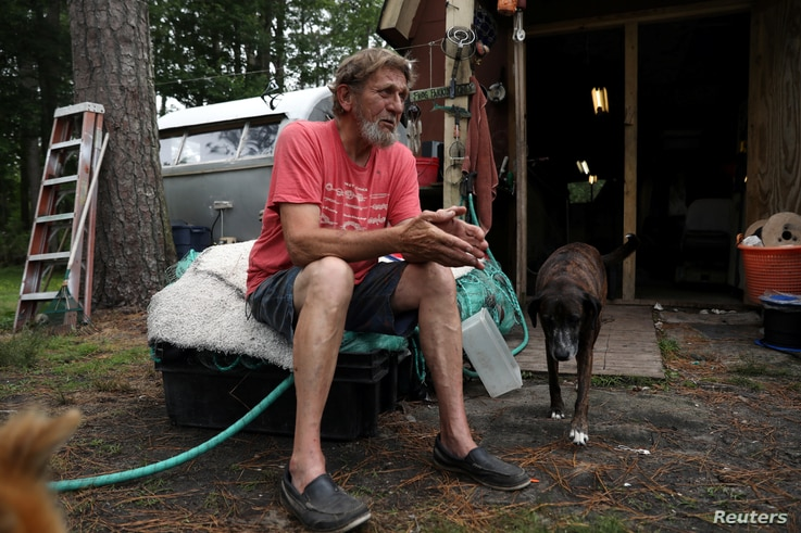 """Karroll """"Frog"""" Tilllett poses outside his workshop near his trailer in Wanchese, North Carolina, May 31, 2017."""