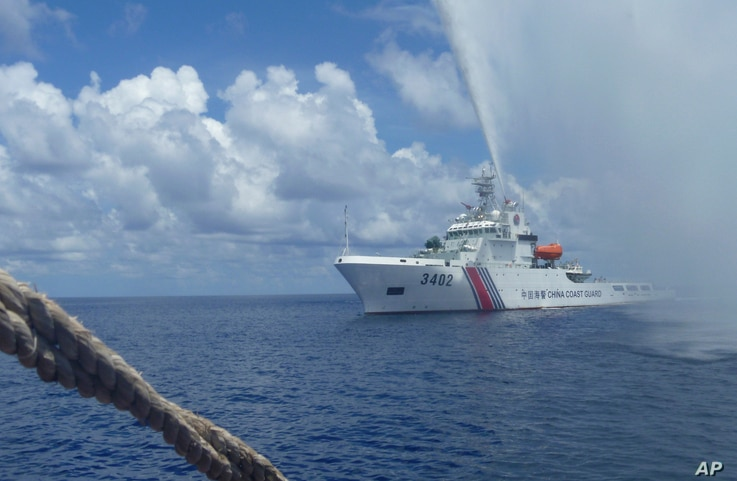 FILE - A Chinese Coast Guard boat approaches a Filipino fishing vessel off Scarborough Shoal in the South China Sea, Sept. 23, 2015.