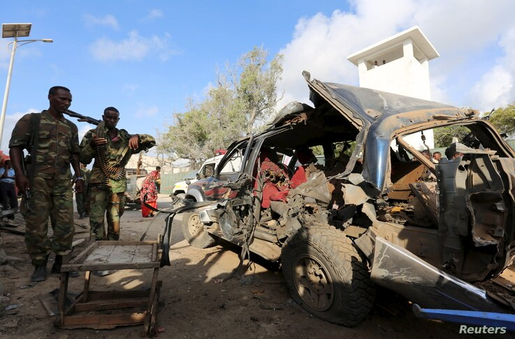 Somali policemen look at the wreckage of a car at the scene of an explosion following an attack in Somalia's capital Mogadishu, March 9, 2016.