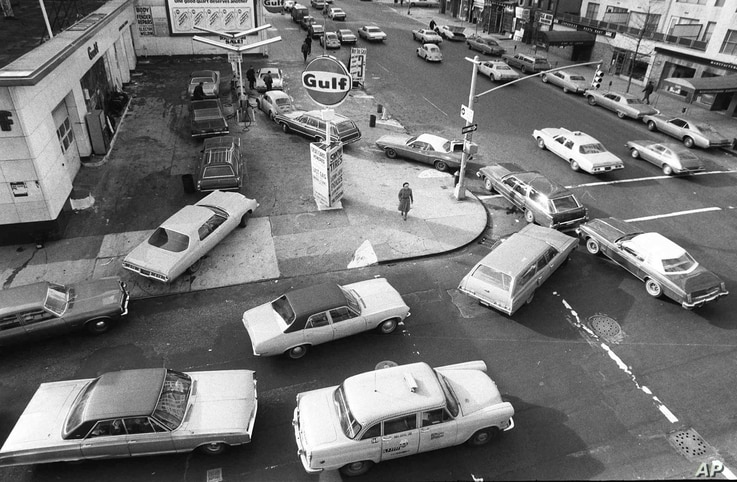 FILE - Cars line up in two directions at a gas station during fuel shortages brought about by an Arab oil embargo, in New York City, Dec. 23, 1973.