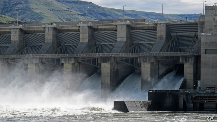 In this April 11, 2018 photo, water moves through a spillway of the Lower Granite Dam on the Snake River near Almota, Washington.