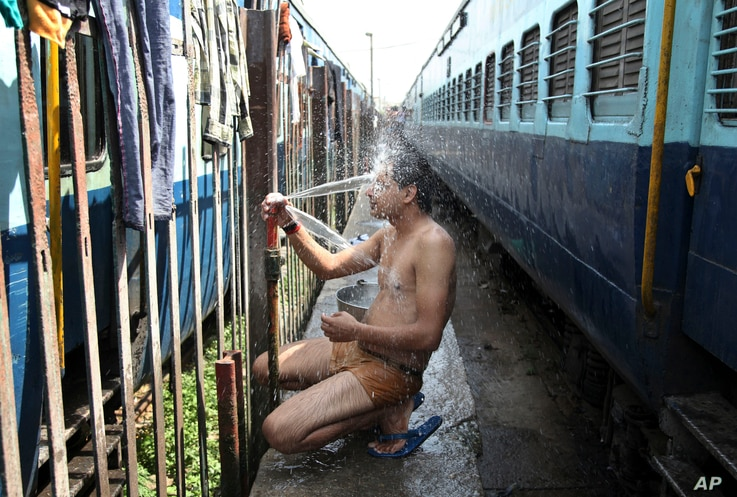 An Indian passenger takes a bath beside rail tracks on a hot summer day at a railway station in Jammu, India, Monday, May 25, 2015. Severe heat wave conditions continue to prevail at several places in northern India with temperatures reaching 48 degr...
