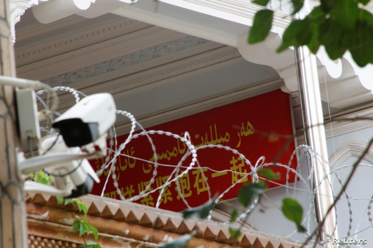 A propaganda banner and a security camera are placed on the walls of a mosque in the Old City in Kashgar, Xinjiang Uighur Autonomous Region, China, Sept. 6, 2018.