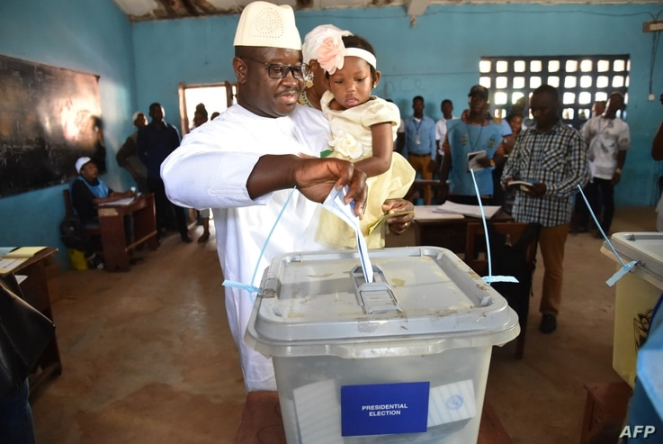 Sierra Leone's People Party presidential candidate Julius Mada Bio holds his daughter while casting his ballot for the general elections, at a polling station in Freetown, March 7, 2018, as his wife looks on.