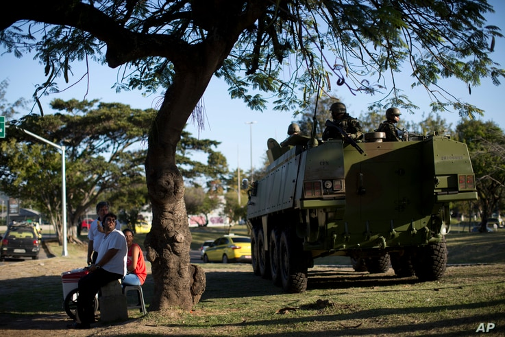 People watch an armored vehicle of Navy soldiers patrol near the Santos Dumont Airport in Rio de Janeiro, Brazil, July 28, 2017.