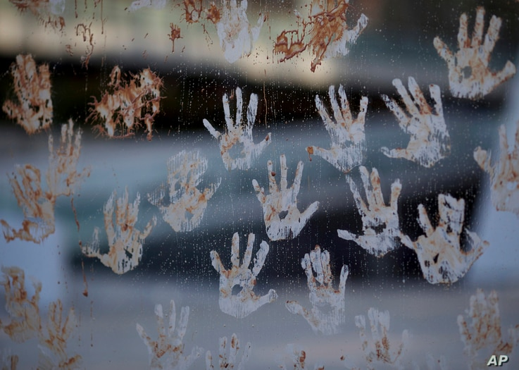 Mud hand prints are seen on a glass window, during a protest at the door of the Brazilian mining company Vale, in Rio de Janeiro, Brazil, Jan. 28, 2019.