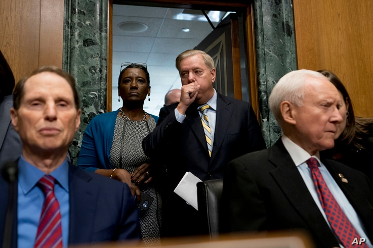 Sen. Lindsey Graham, R-S.C., center, arrives to speak at a Senate Finance Committee hearing to consider the Graham-Cassidy healthcare proposal, Sept. 25, 2017, in Washington. Also pictured is Ranking Member Sen. Ron Wyden, D-Ore., left, and Chairman ...
