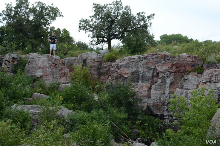 Mikah stands above a pipestone quarry. Native Americans use the red stone to make ceremonial pipes.