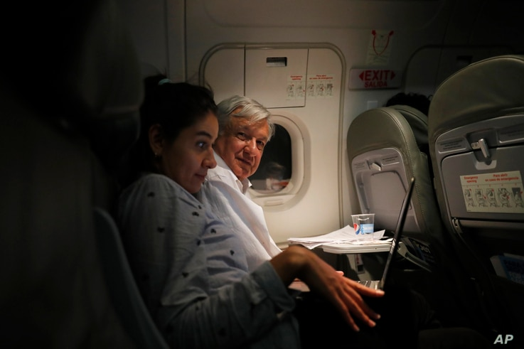 Mexican President Andres Manuel Lopez Obrador, center, sits with an assistant as he travels in economy class aboard a commercial flight from Guadalajara to Mexico City, March 9, 2019.