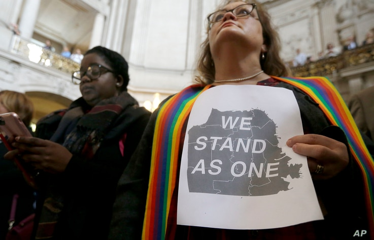 The Rev. Annie Steinberg-Behrman (right) provisional pastor with Metropolitan Community Church, holds a sign while listening to speakers at a meeting at City Hall in San Francisco to reaffirm the city's commitment to being a sanctuary city, Nov. 14,