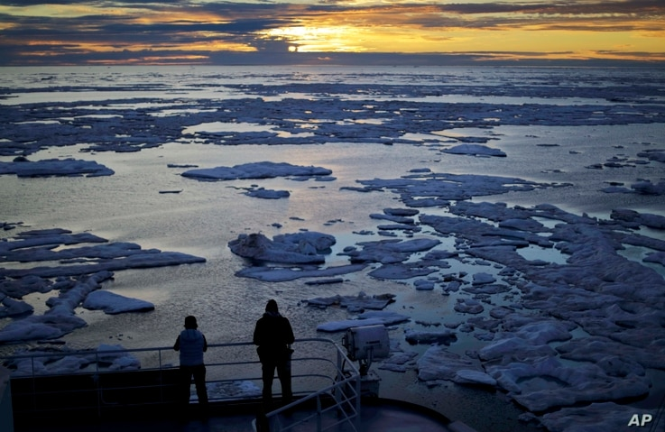 FILE - Researchers look out from the Finnish icebreaker MSV Nordica as the sun sets over sea ice in the Victoria Strait along the Northwest Passage in the Canadian Arctic Archipelago, July 21, 2017.