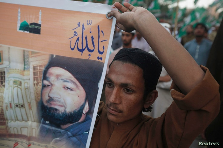 A supporter of a religious political party holds a banner of convicted killer Mumtaz Qadri during a demonstration against Qadri's sentence, in Karachi, Pakistan, March 9, 2015.