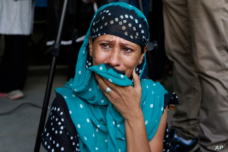 A relative of a an Indian man convicted for the 2002 Gujarat riots cries after the court announced the lengths of the sentences in Ahmadabad, India on June 17, 2016.