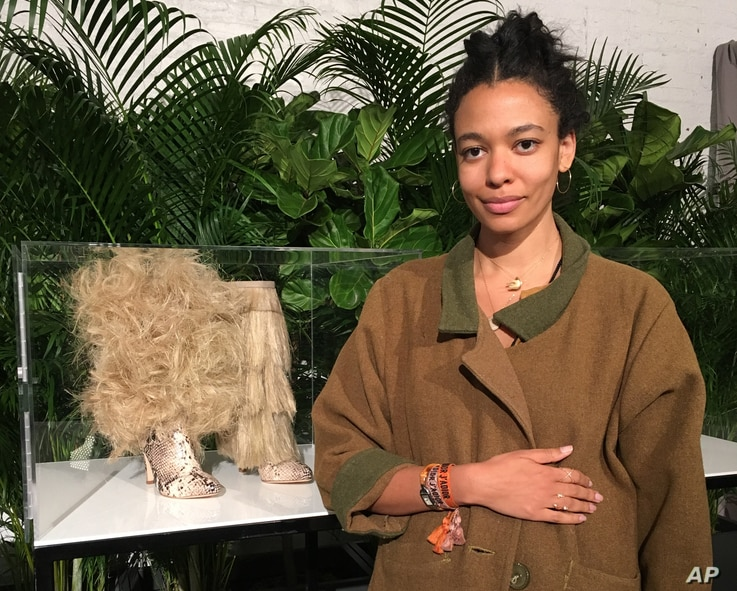 """Aurora James, founder of the footwear brand Brother Vellies, poses with a couple of shoe designs inspired by Africa and the superhero film, """"Black Panther,"""" Feb. 12, 2018 in New York. The company uses artisans in several African countries to crea..."""