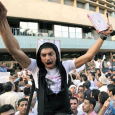 """A man carries a Koran and a cross during a demonstration by Egyptian Christians and Muslims shouting """"Muslims and Christians hand in hand"""" in front of the Egyptian Television building in downtown Cairo, May 8, 2011"""