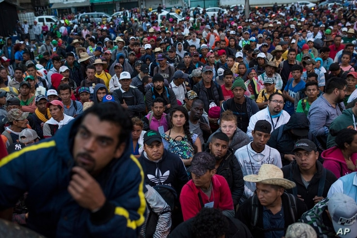 Central American migrants, part of one of the caravans hoping to reach the U.S. border, listen to a coordinator during the early-morning hours in Sayula de Aleman, Veracruz state, Mexico, Nov. 3, 2018.