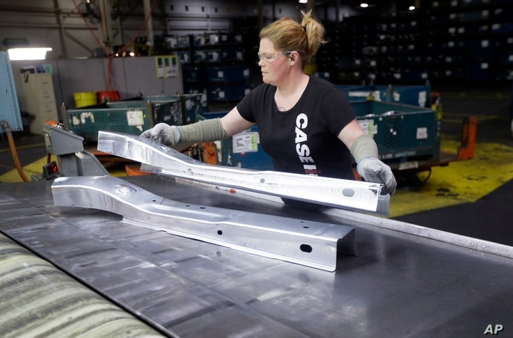 FILE - United Auto Workers line worker Crystal McIntyre unloads parts from a stamping machine at the General Motors Pontiac Metal Center in Pontiac, Mich., April 30, 2015.
