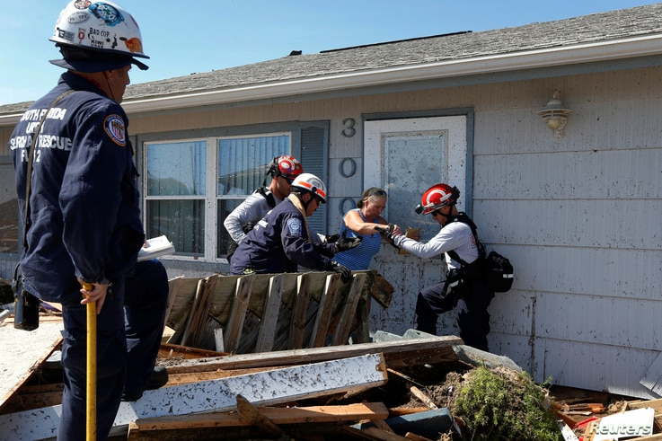 Bianna Kelsay is rescued from a building damaged by Hurricane Michael in Mexico Beach, Florida, U.S., Oct. 11, 2018.