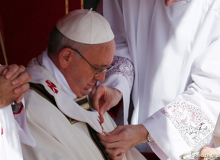 The pallium is fitted on Pope Francis during his inaugural mass in Saint Peter's Square at the Vatican, Mar. 19, 2013.