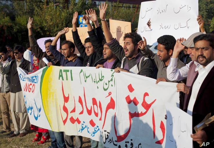 "Pakistani students shout slogans against the Islamic State group holding a banner that reads ""down with Islamic State rally,"" in Islamabad, Nov 20, 2014."