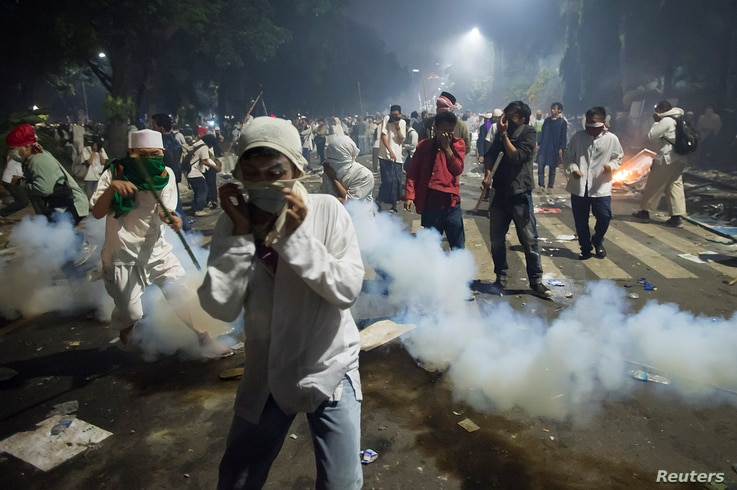 Muslim hardline protesters cover their faces as police fire tear gas during a protest against Jakarta's incumbent governor Basuki Tjahaja Purnama, an ethnic Chinese Christian running in the upcoming election, Nov. 4, 2016.
