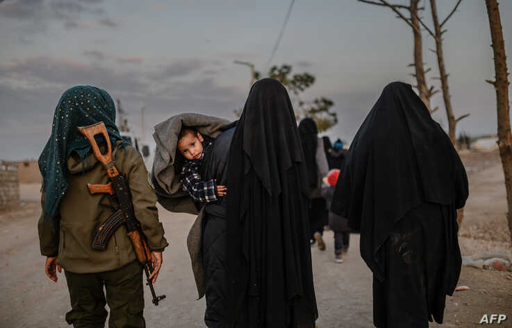 Veiled women, reportedly wives and members of the Islamic State, walk under the supervision of a female fighter from the Syrian Democratic Forces (SDF) at al-Hol camp in al-Hasakeh governorate in northeastern Syria on February 17, 2019.