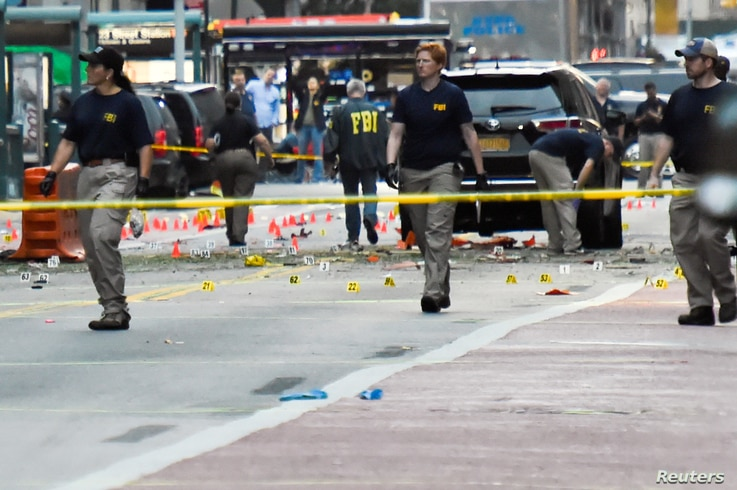 Federal Bureau of Investigation (FBI) officials walk past evidence markers near the site of an explosion in the Chelsea neighborhood of Manhattan, New York, Sept. 18, 2016.