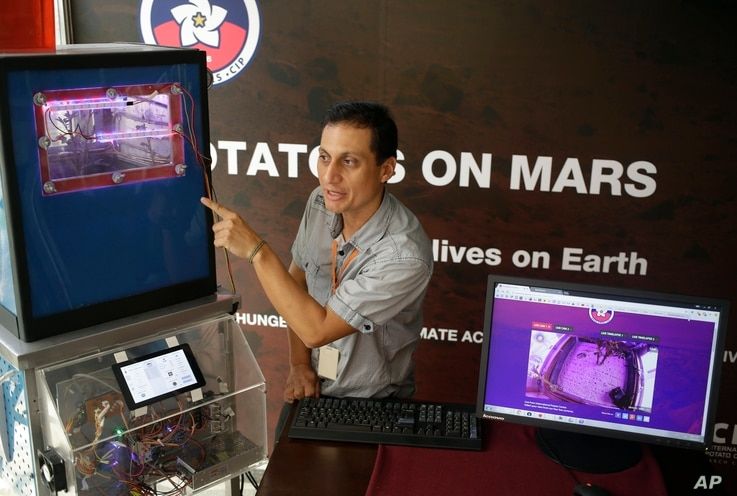 Peruvian scientist David Ramirez points to a potato plant in a simulator that produces conditions similar to those of Mars, in Lima Peru, March 16, 2017.