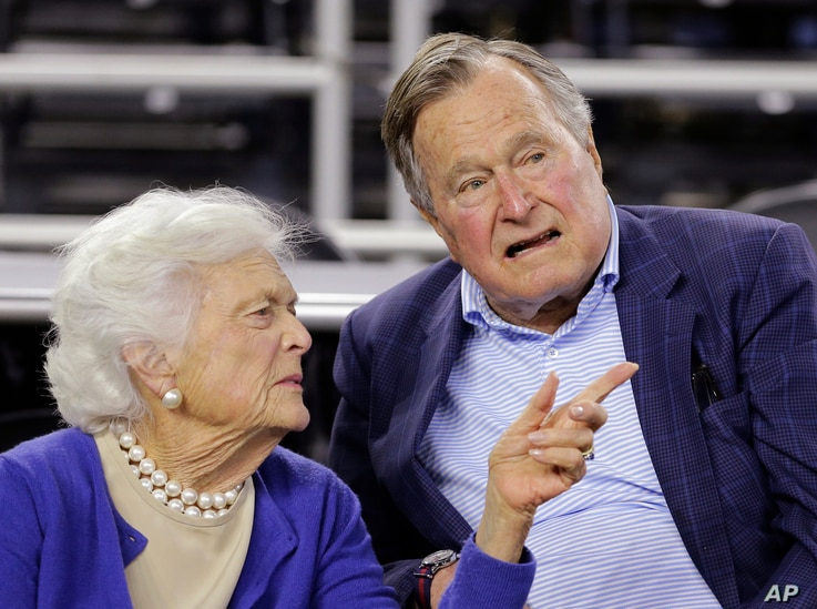 FILE - Former president George H.W. Bush and his wife, Barbara Bush, are seen at a college basketball game in Houston, Texas, March 29, 2015.