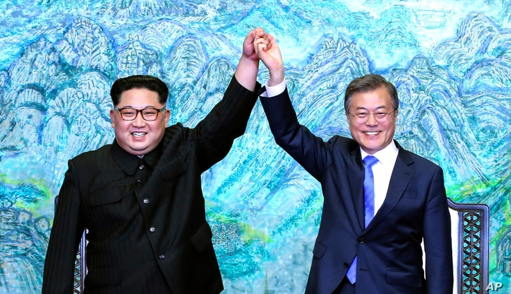 North Korean leader Kim Jong Un, left, and South Korean President Moon Jae-in raise their hands after signing a joint statement at the border village of Panmunjom in the Demilitarized Zone, South Korea, April 27, 2018.