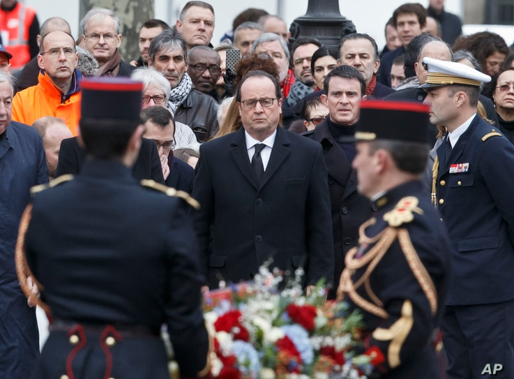France's President Francois Hollande, left, and Prime Minister Manuel Valls, right, lay a wreath of flowers during a ceremony to honor the victims of the Islamic extremist attacks at Place de la Republique in Paris, Jan. 10, 2016.