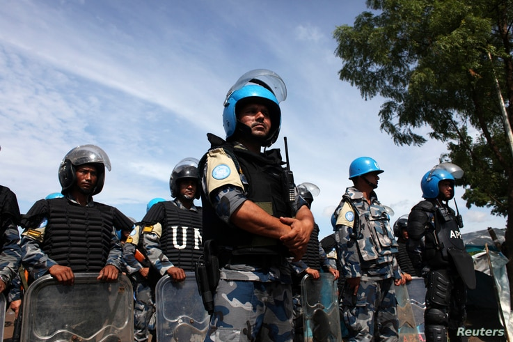 FILE - U.N. peacekeepers stand guard during a visit by U.N. Secretary-General Ban Ki-moon to an internally displaced persons camp at an UNMISS base in Juba May 6, 2014. Kenya announced Wednesday that it will immediately pull its 1,000 peacekeepers ou