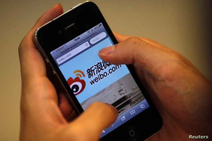 A man holds an iPhone as he visits Sina's Weibo microblogging site in Shanghai May 29, 2012. China's Sina Corp has introduced a code of conduct for users of the local version of Twitter amid accusations of censorship to rein in what has grown into a ...