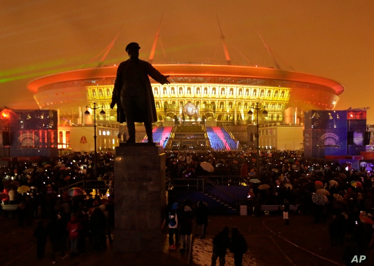 People watch a light show at the new soccer stadium on Krestovsky Island, which will host some 2018 World Cup and 2017 Confederations Cup matches, in St. Petersburg, Russia, April 22, 2017. A statue of Sergei Kirov, an early Bolshevik leader, is in t
