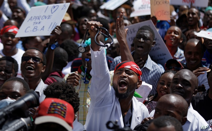 FILE - A doctor holds his stethoscope in the air as he and other medical staff protest the detention of their union leaders, outside an appeal court in Nairobi, Kenya, Feb. 15, 2017.