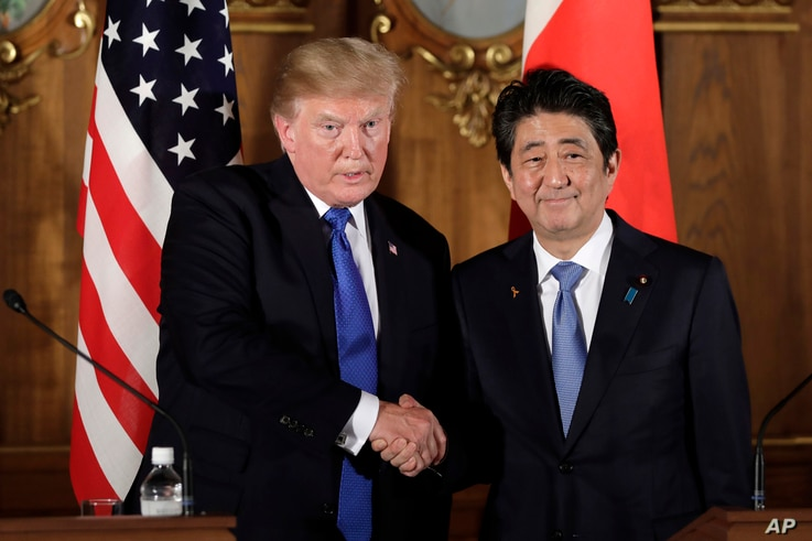 President Donald Trump, left,  shakes hands with Japanese Prime Minister Shinzo Abe during a joint news conference at the Akasaka Palace, Monday, Nov. 6, 2017, in Tokyo.