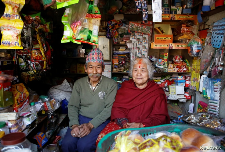 Nhuchhe Bahadur Amatya, 76, a retired accountant at Nepal Electricity Authority, along with his wife, Raywoti Devi Amatya, 74, a housewife, pose for a picture as they sit inside their shop in Lalitpur, Nepal, Feb. 4, 2018. Nhuchhe was 17 and Raywoti ...