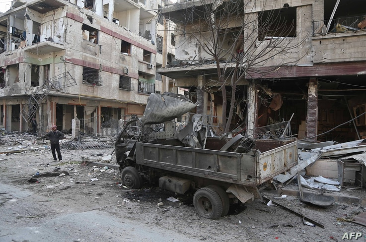 A Syrian man pauses near destruction following a reported regime air strike in the rebel-held town of Hamouria, in the besieged Eastern Ghouta region on the outskirts of the capital Damascus, Feb. 21, 2018.