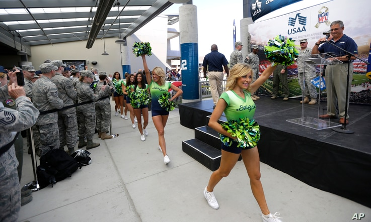 Seattle Seahawks NFL football Sea Gals cheerleaders greet troops at Joint Base Lewis-McChord, Wash. before a ceremony to transfer the team's 12th Man Flag from U.S. Army soldiers who have returned from Afghanistan to U.S. Air Force air crews who fl...