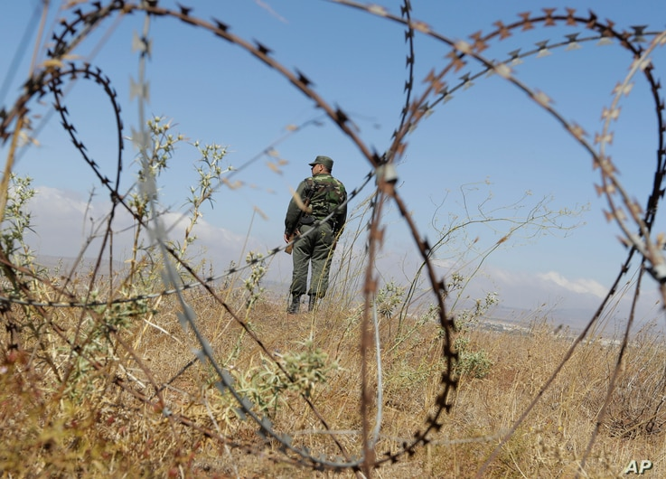 A Syrian army soldier stands guard near the village of Tal Kroum, Syria, Aug. 14, 2018. The Russian military said Tuesday that its forces in Syria will help U.N. peacekeepers fully restore patrols along the frontier with the Israeli-occupied Golan He...