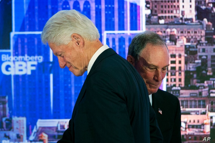 Former U.S. President Bill Clinton, left, passes former New York Mayor Michael Bloomberg after he was introduced as a speaker at the Bloomberg Global Business Forum, Sept. 20, 2017, in New York.