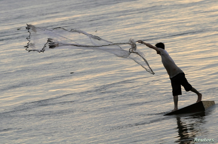 FILE - A man casts a fishing net on the bank of the Mekong river in Phnom Penh.