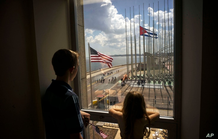 Children look out a window from inside the newly opened U.S. Embassy, at the end of a flag raising ceremony, in Havana, Cuba, Aug. 14, 2015.