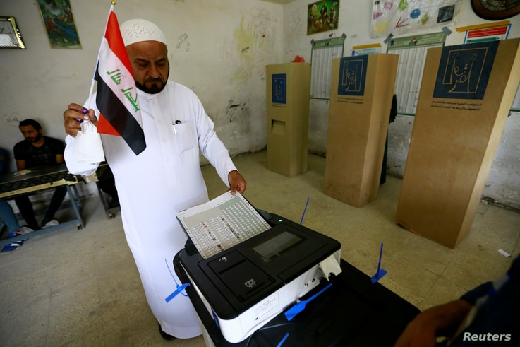 An Iraqi man casts his vote electronically at a polling station during the parliamentary election in Baghdad, May 12, 2018.