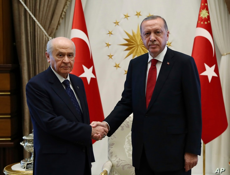 Devlet Bahceli, left, leader of Nationalist Movement Party, or MHP, and the main ally of Turkey's President Recep Tayyip Erdogan, right, shake hands before a meeting at the presidential palace in Ankara, Turkey, June 27, 2018.