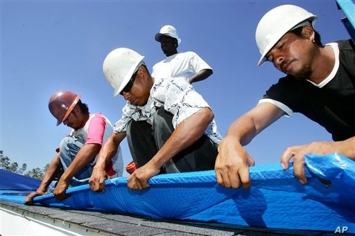 Immigrant workers, from left, Marcos Jamangape, Abel Tapia, Jack Horne, standing, and Joaquin Garcia install a plastic tarp as temporary protection Oct. 23, 2005, for a home damaged by Hurricane Katrina in Gulfport, Miss.  (AP Photo/Marcio Jose Sanch...