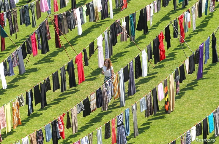 """A woman walks among dresses and skirts hanging inside a stadium, in an art exhibition titled """"Thinking of You"""" by Kosovo-born, London-based artist Alketa Xhafa-Mripa, in Pristina, June 12, 2015. Dresses and skirts donated by Cherie Blair and Rita Ora..."""
