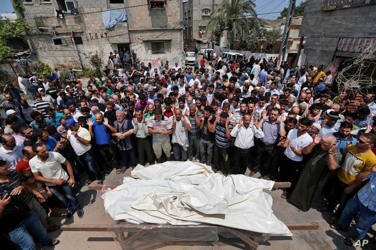 Mourners pray in front of the bodies of seven members of the Kelani family, killed overnight by an Israeli strike in Gaza City, during their funeral in Beit Lahiya, northern Gaza Strip, on Tuesday, July 22, 2014. Ibrahim Kelani, 53, his wife Taghreed