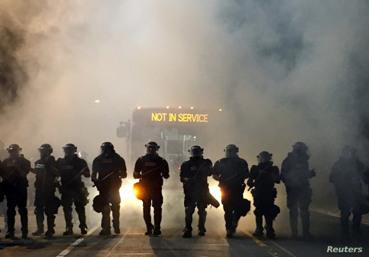 Police officers wearing riot gear block a road during protests after police fatally shot Keith Lamont Scott in the parking lot of an apartment complex in Charlotte, North Carolina, Sept. 20, 2016.