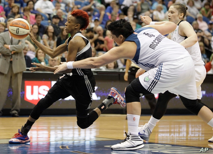 San Antonio Stars guard Danielle Robinson, left, pushes the ball through the Minnesota Lynx defense in a game in Minneapolis, July 3, 2014.
